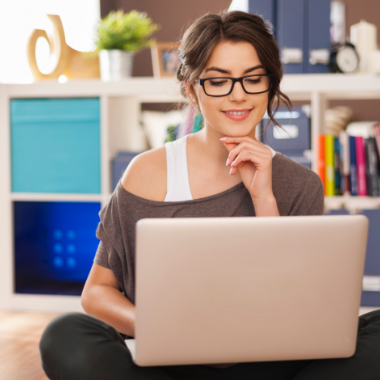 smiling-woman-using-laptop-on-floor-at-home-KTWBEPN.png